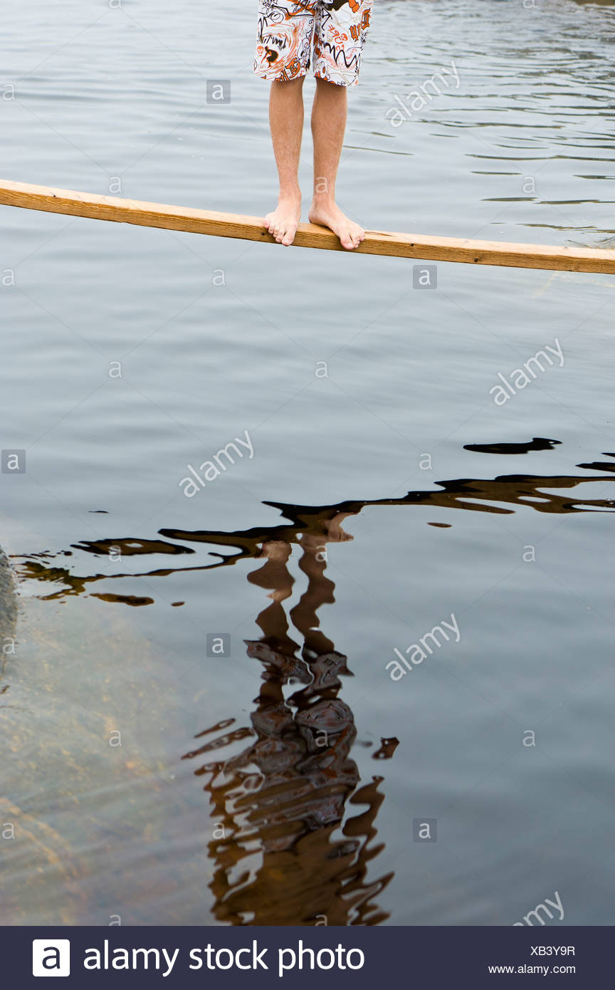 Low section of bare feet standing on a plank over the water - Stock Image