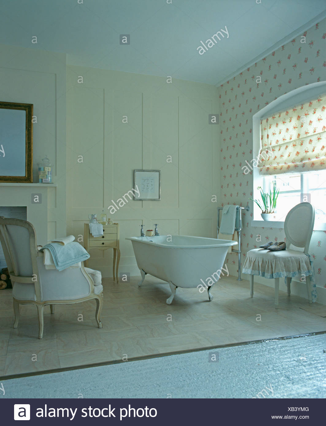 Roll-top bath and rose-patterned blind in country bathroom with ...