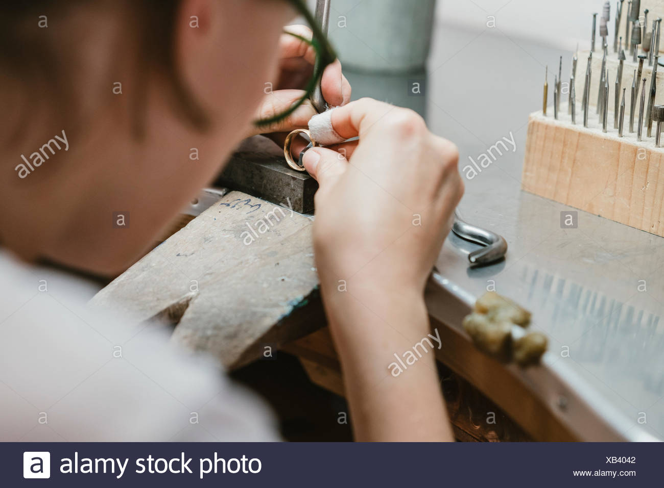 Over shoulder view of female jeweller making ring at workbench - Stock Image