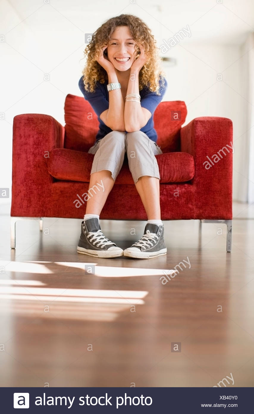 Woman sitting in armchair - Stock Image