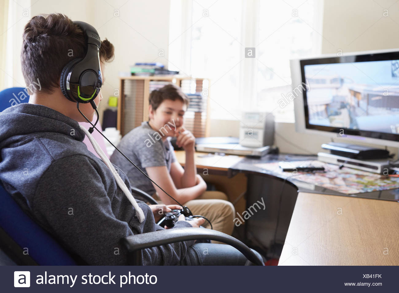 Two boys playing on computer game - Stock Image