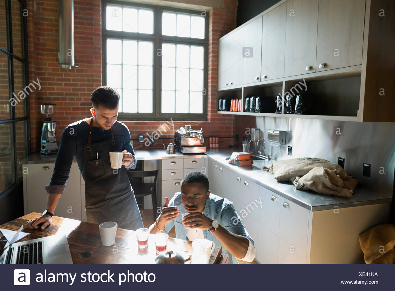 Entrepreneurial coffee roasters testing coffee in kitchen - Stock Image