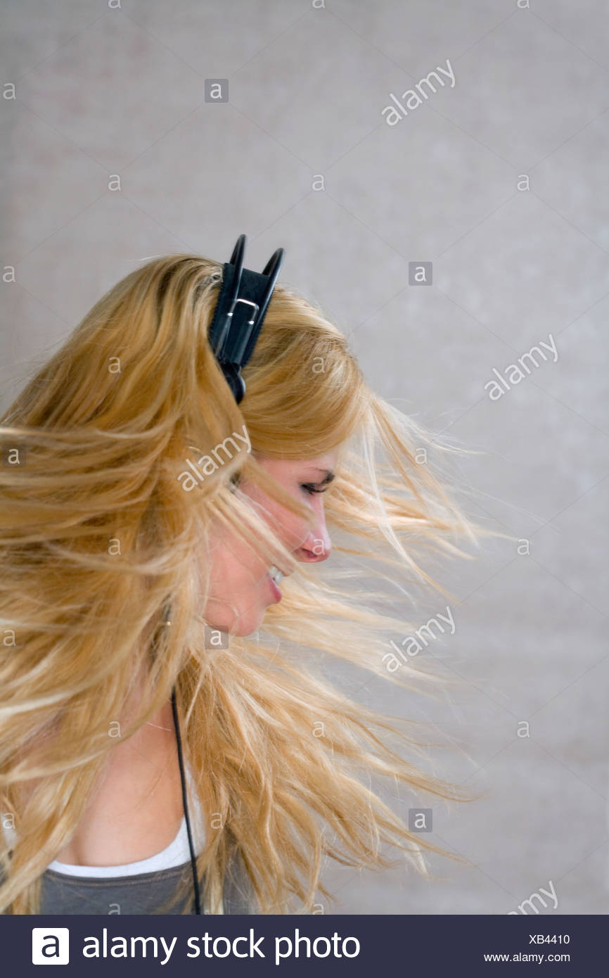 Young woman moves with headphones - Stock Image