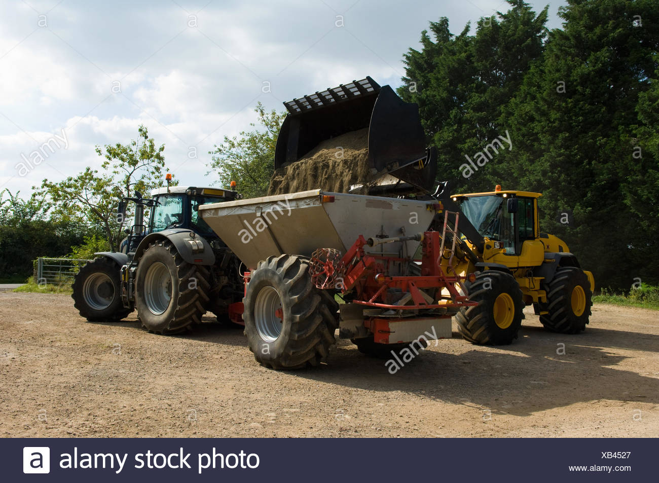 Farmer transferring organic fertilizer into fertilizer spreader in farm yard - Stock Image