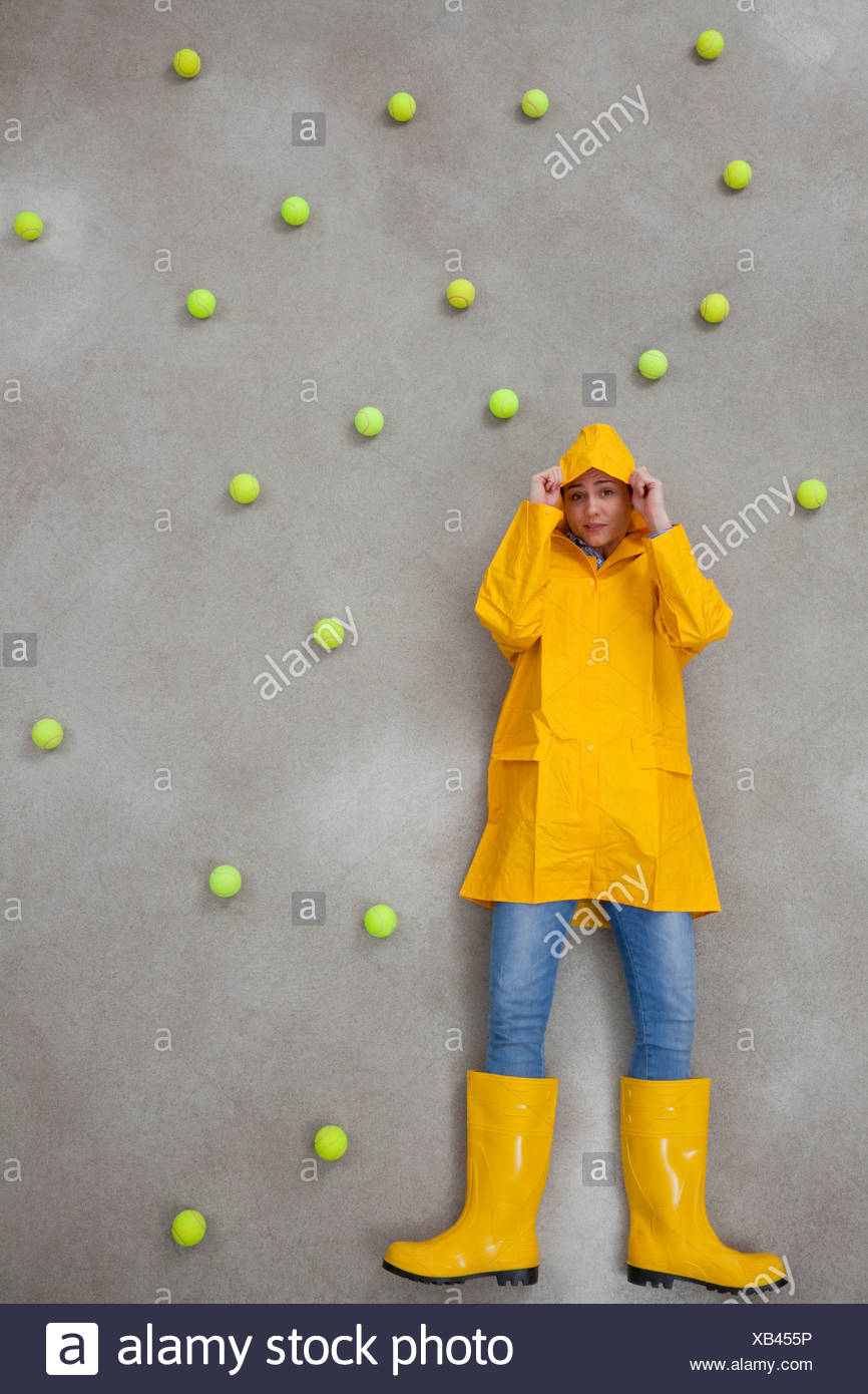 Mid adult woman wearing rain coat and rubber boots in acid rain - Stock Image
