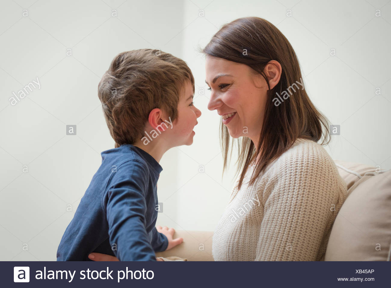 Mother and son smiling at each other, face to face - Stock Image