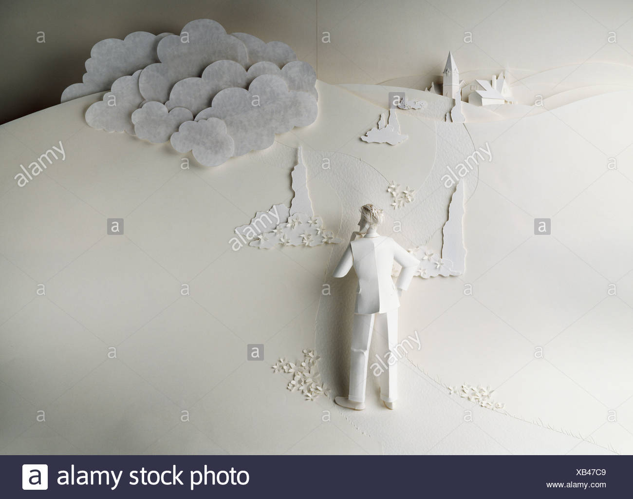 Paper artwork; 3 dimensional paper man standing with hand on hip, other hand on chin, puzzled stance - Stock Image