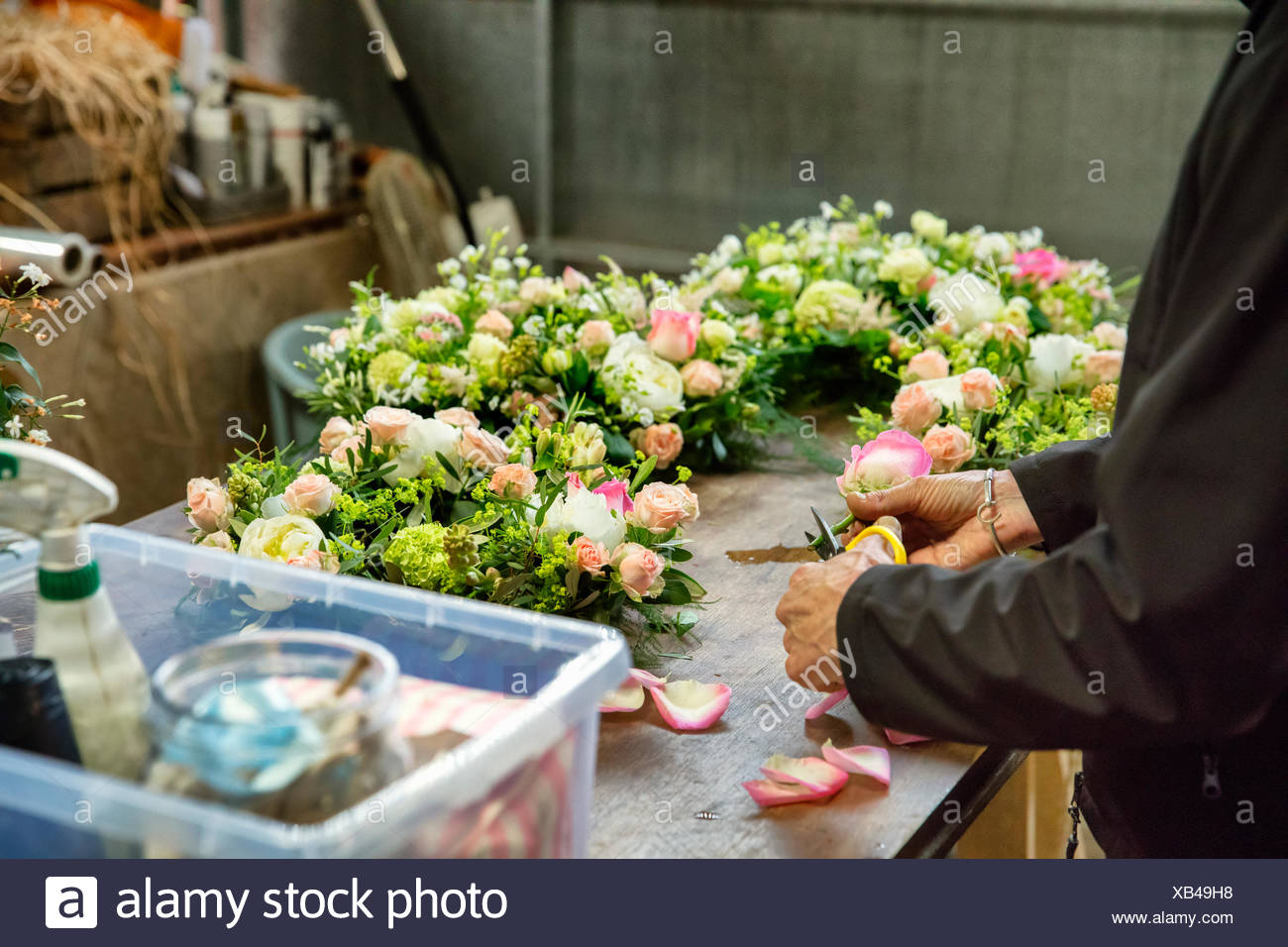 Commercial florist. A woman working on  a floral decoration  at a workbench. - Stock Image