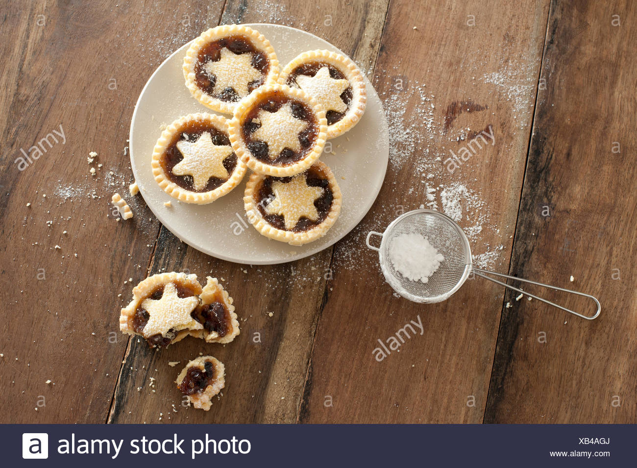 Overhead view of a plate of decorative freshly baked Christmas mince pies with pastry stars alongside & Half Eaten Mince Pie Stock Photos u0026 Half Eaten Mince Pie Stock ...