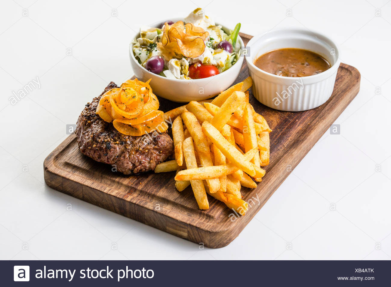 Wild steak with braised onions, French fries and a small salad - Stock Image