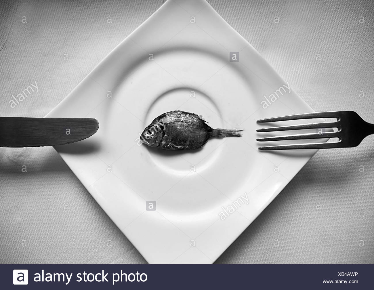 Small fish on a plate with cutlery - Stock Image