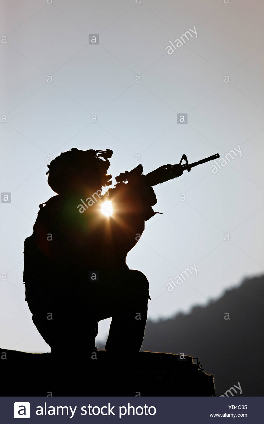U.S. Army Soldier Holding His Weapon at Sunrise - Stock Image