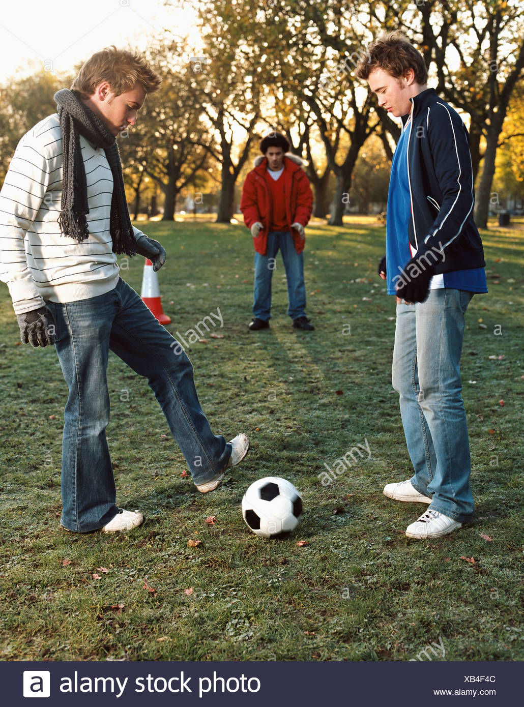 Men playing football in park - Stock Image