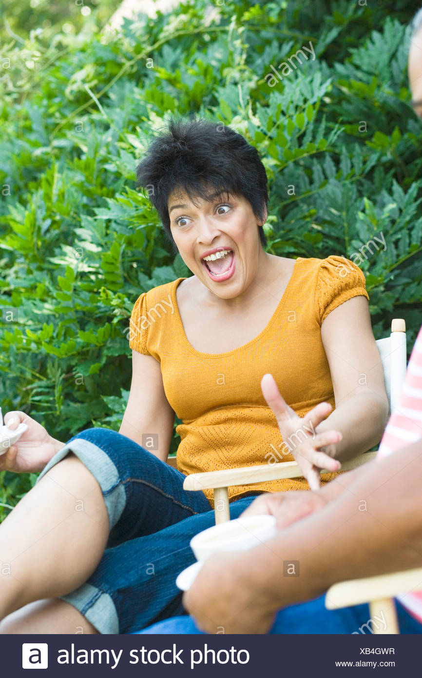 Mature woman sitting on a chair and shouting - Stock Image