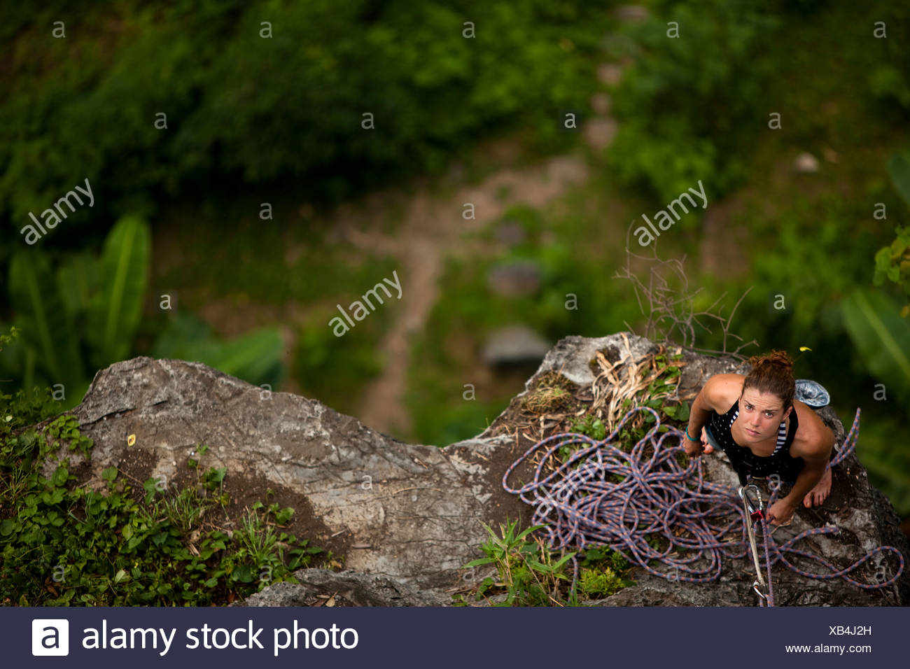 Caucasian female climer looking up from belay station 60 metres above in rural Asia. - Stock Image