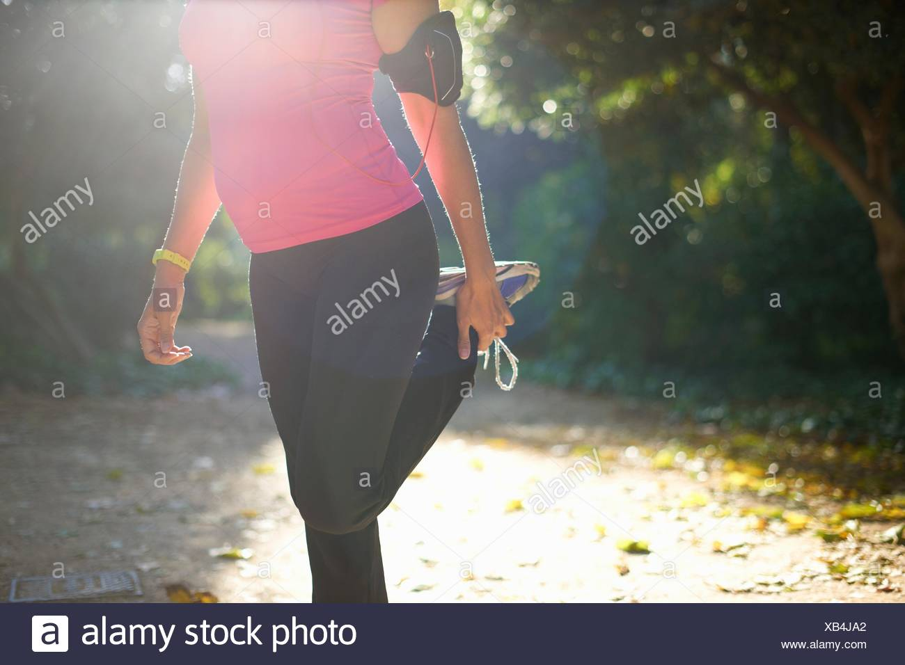 Chest down of mature woman wearing sports clothing, holding ankle stretching leg - Stock Image