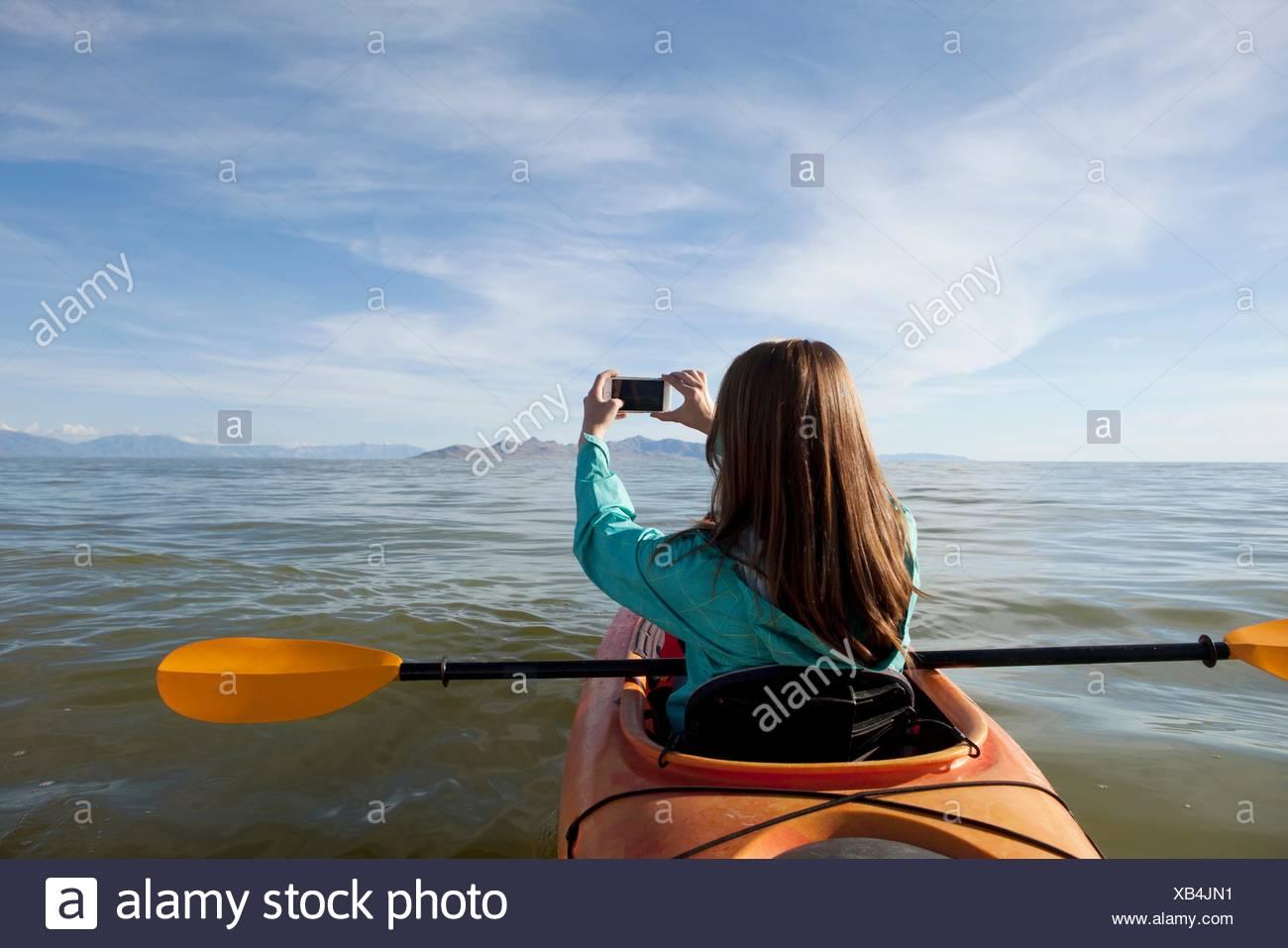 Rear view of young woman in kayak taking photograph, Great Salt Lake, Utah, USA Stock Photo