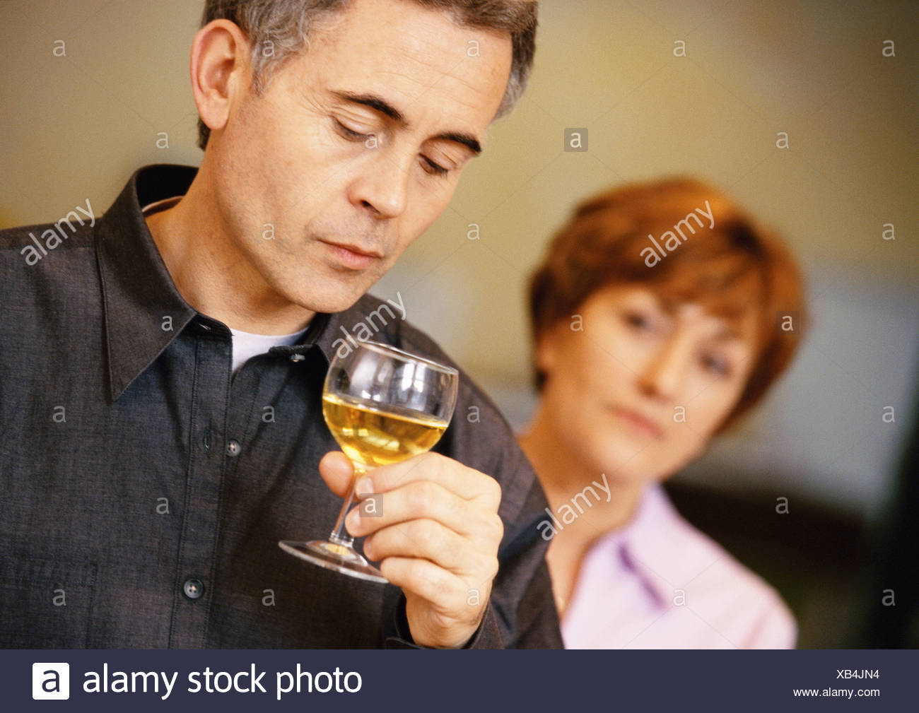 Man holding and looking at wine glass, woman blurred in background, head and shoulders, close-up - Stock Image