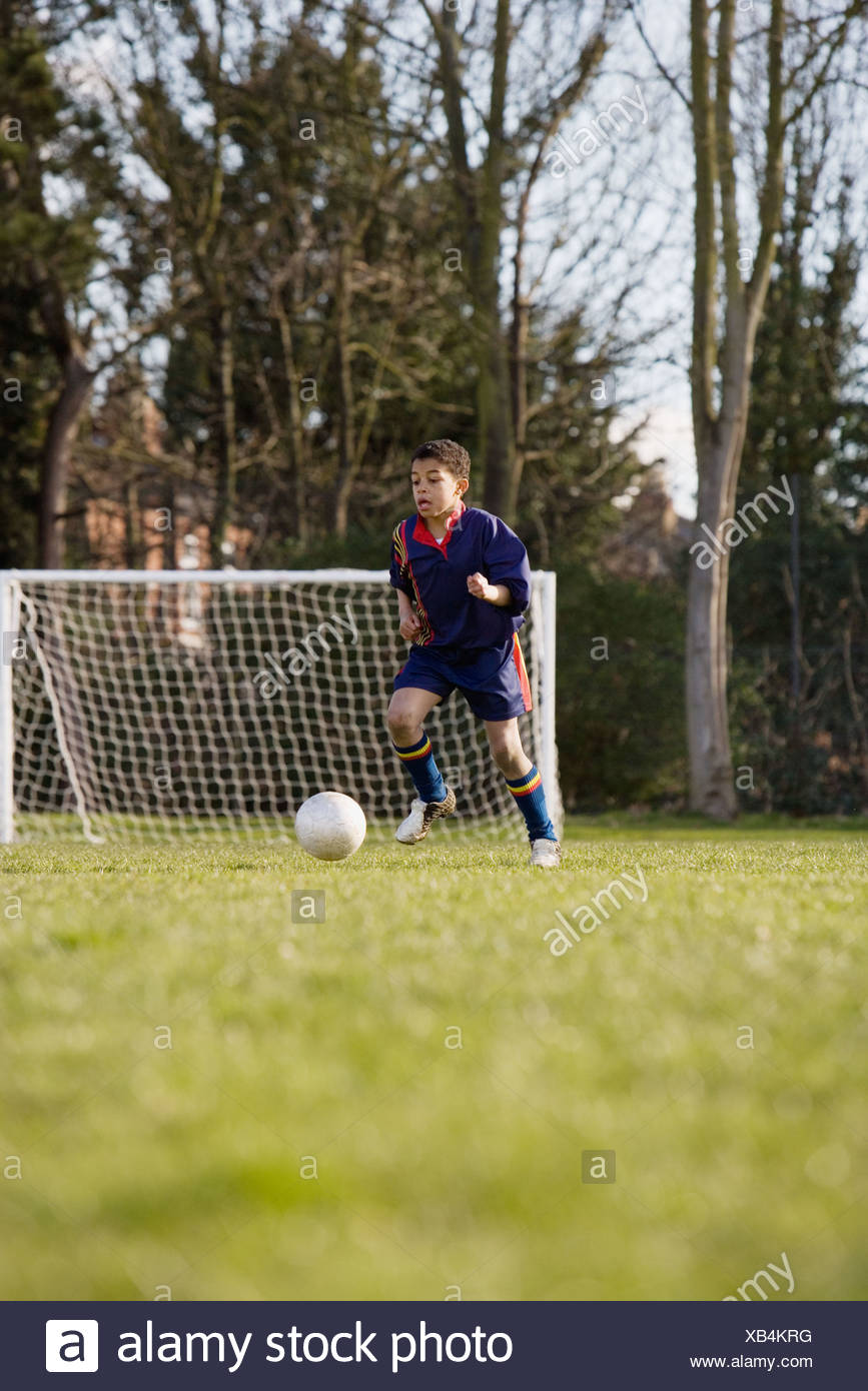 Boy kicking football - Stock Image