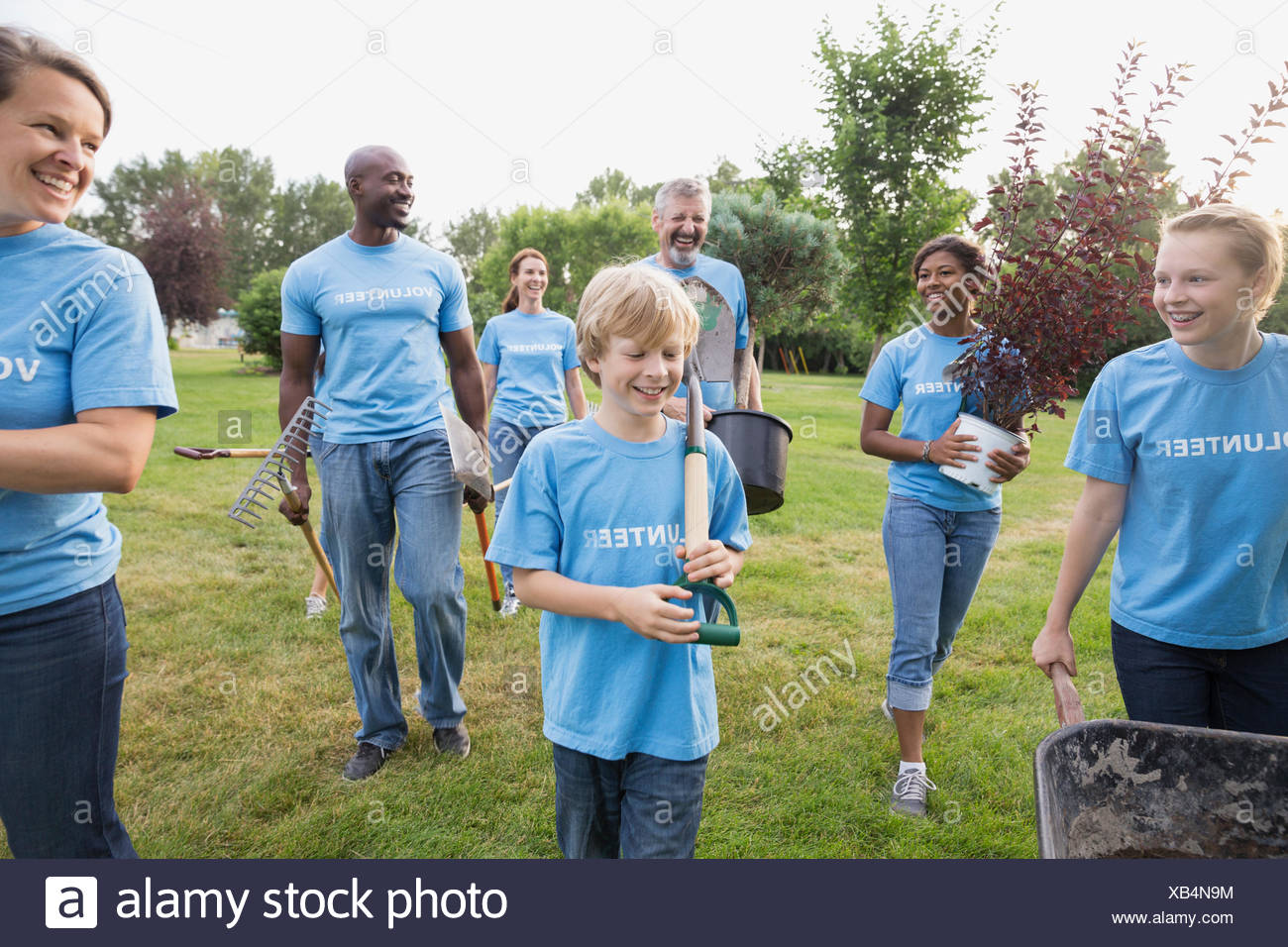 Volunteers carrying potted plant and tools - Stock Image