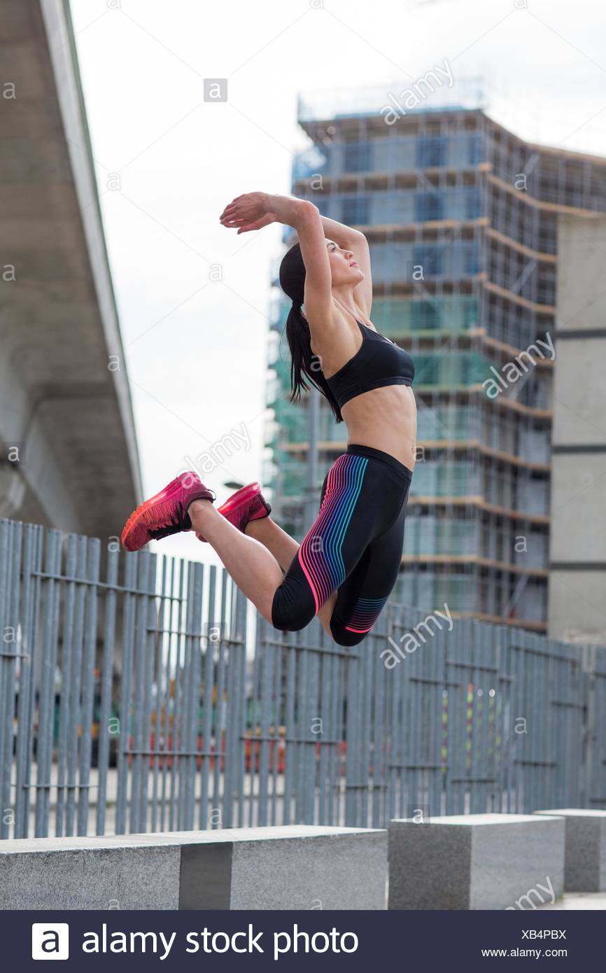MODEL RELEASED. Young woman jumping mid air. - Stock Image