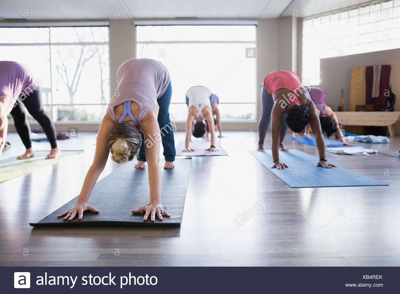 Women practicing downward facing dog in yoga class - Stock Image