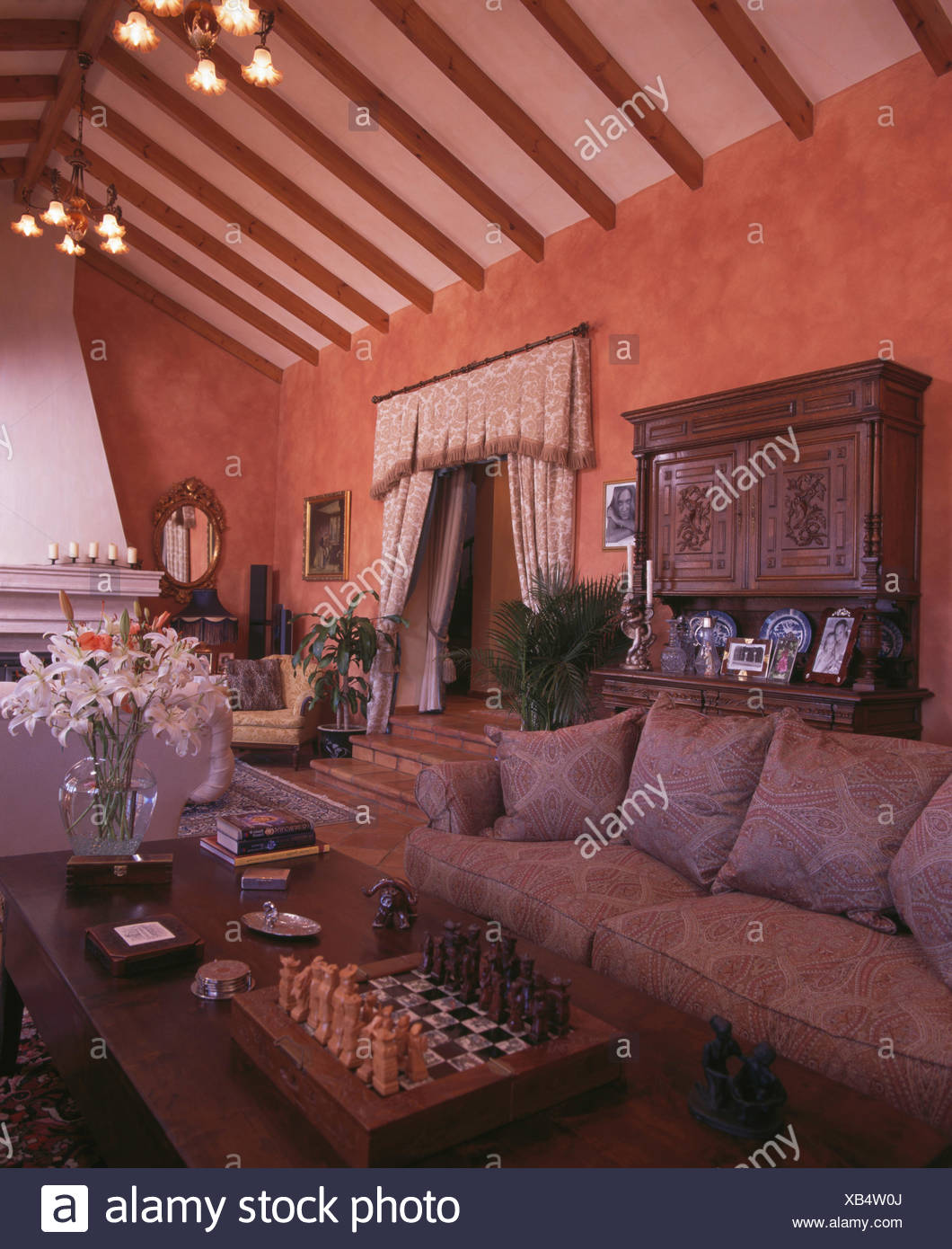 Pale Grey Sofa Beside Table With A Chess Set In Terracotta