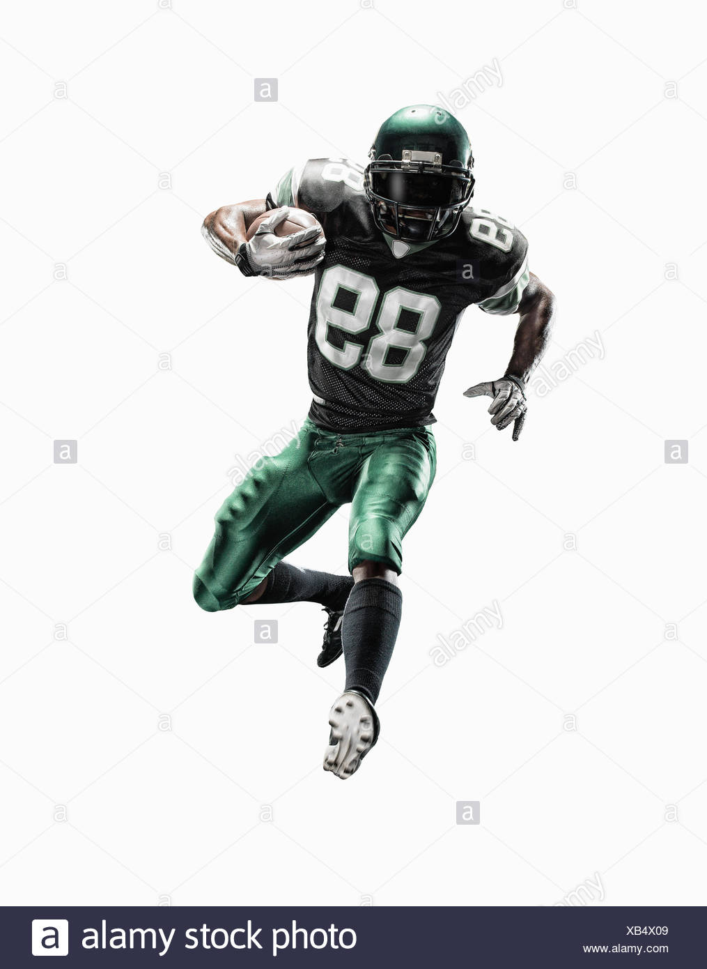 Studio shot of young male football player running with ball - Stock Image