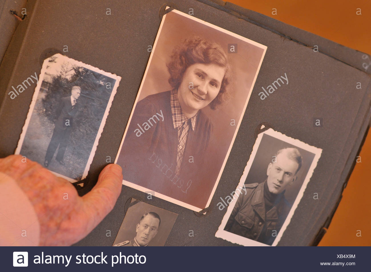 Elderly woman looking through photo album filled with old family portraits - Stock Image