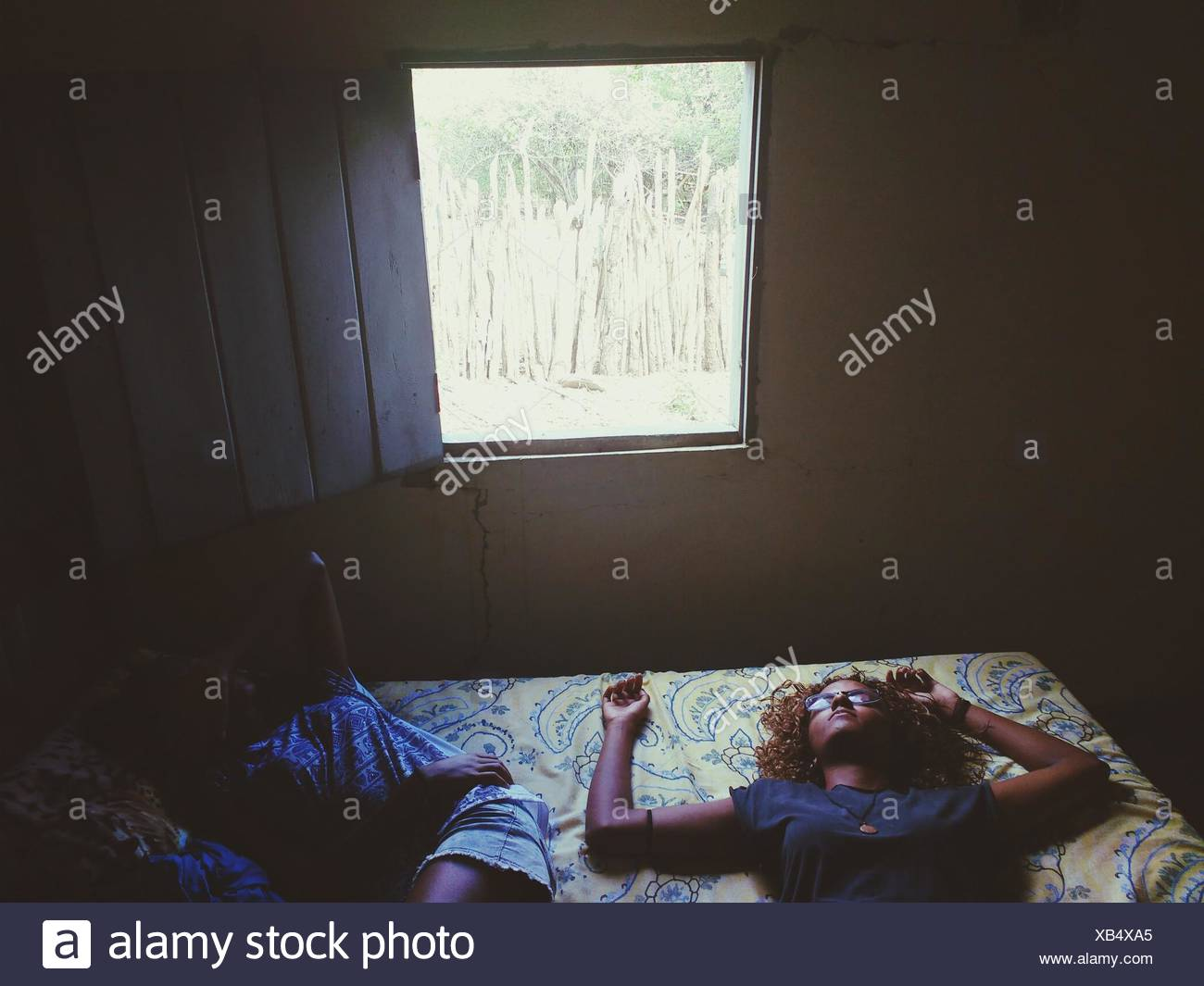 Friends Sleeping On Bed At Home - Stock Image