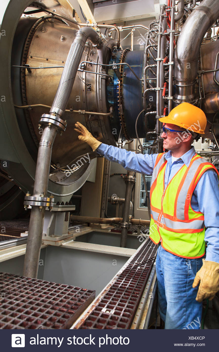 Engineer at fuel ignition stage of gas turbine which drives generators in power plant while turbine is powered down - Stock Image