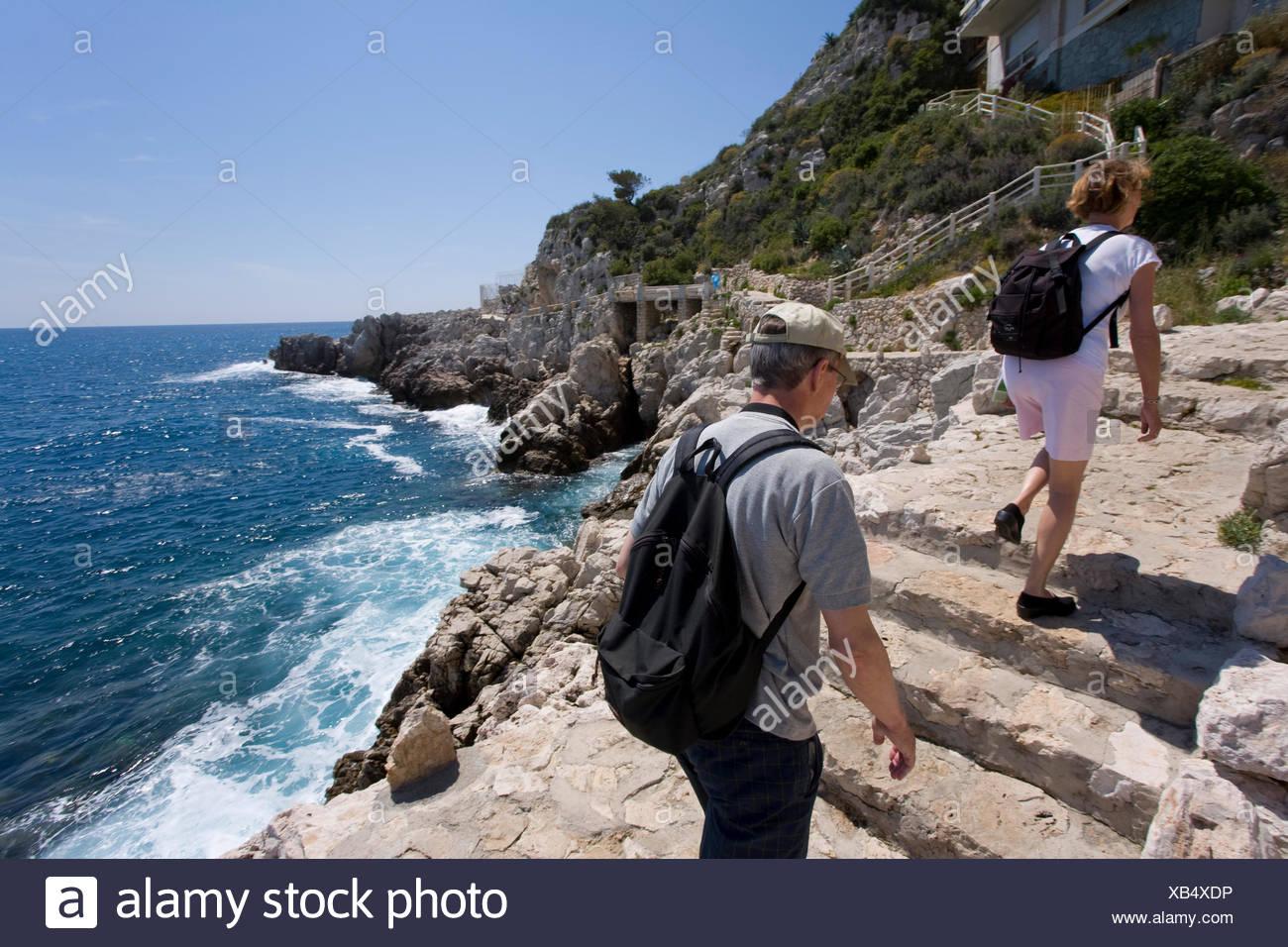 Pedestrians on the Sentier du Bord de Mer coastal path, Nice, Cote d'Azur, France - Stock Image