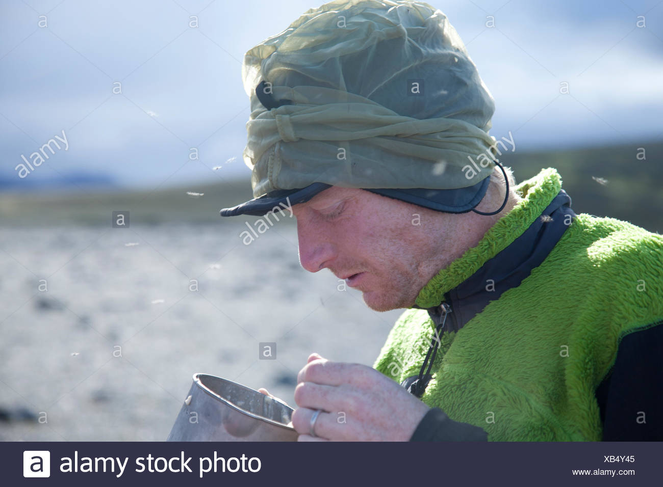 Young man eating breakfeast while camping Stock Photo