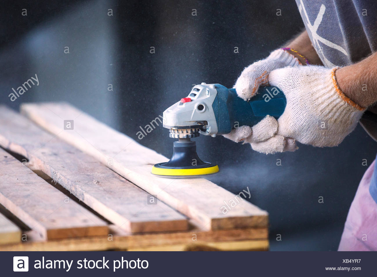 Man sanding wood with a random orbital sander - Stock Image