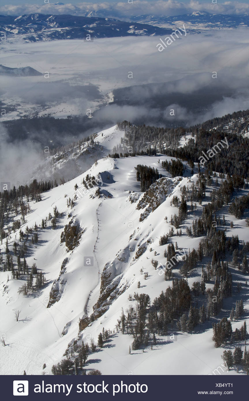 A line of skiers hikes to reach slopes above the lifts at Jackson Hole. - Stock Image
