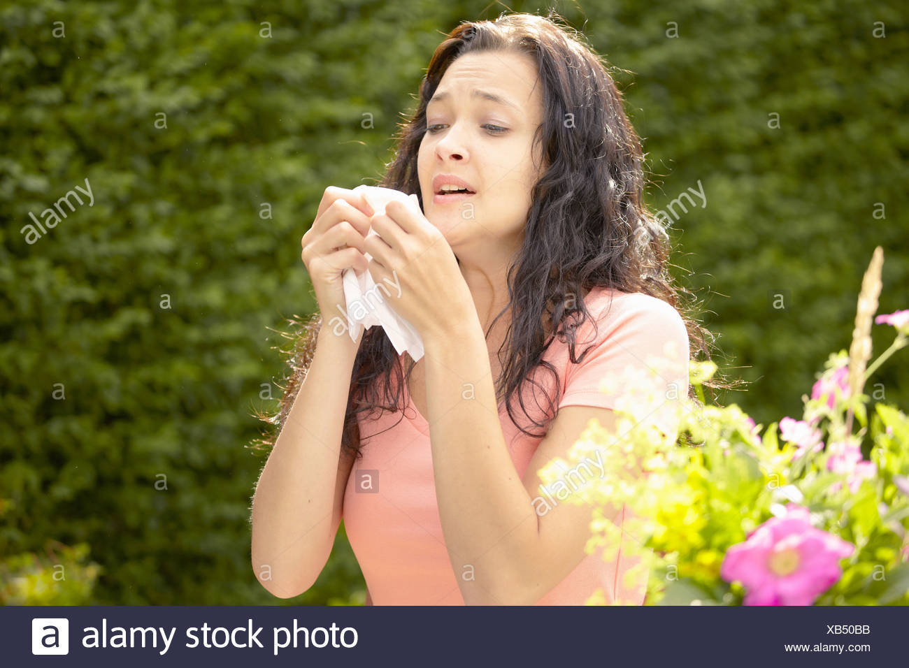 Girl about to sneeze into tissue - Stock Image