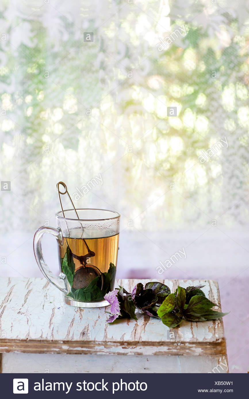 Glass cup of hot herbal tea with bunch of fresh violet basil, served with vintage tea-strainer on old wooden stool with window a - Stock Image