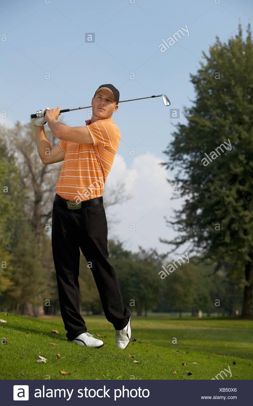 Young man swinging golf club - Stock Image