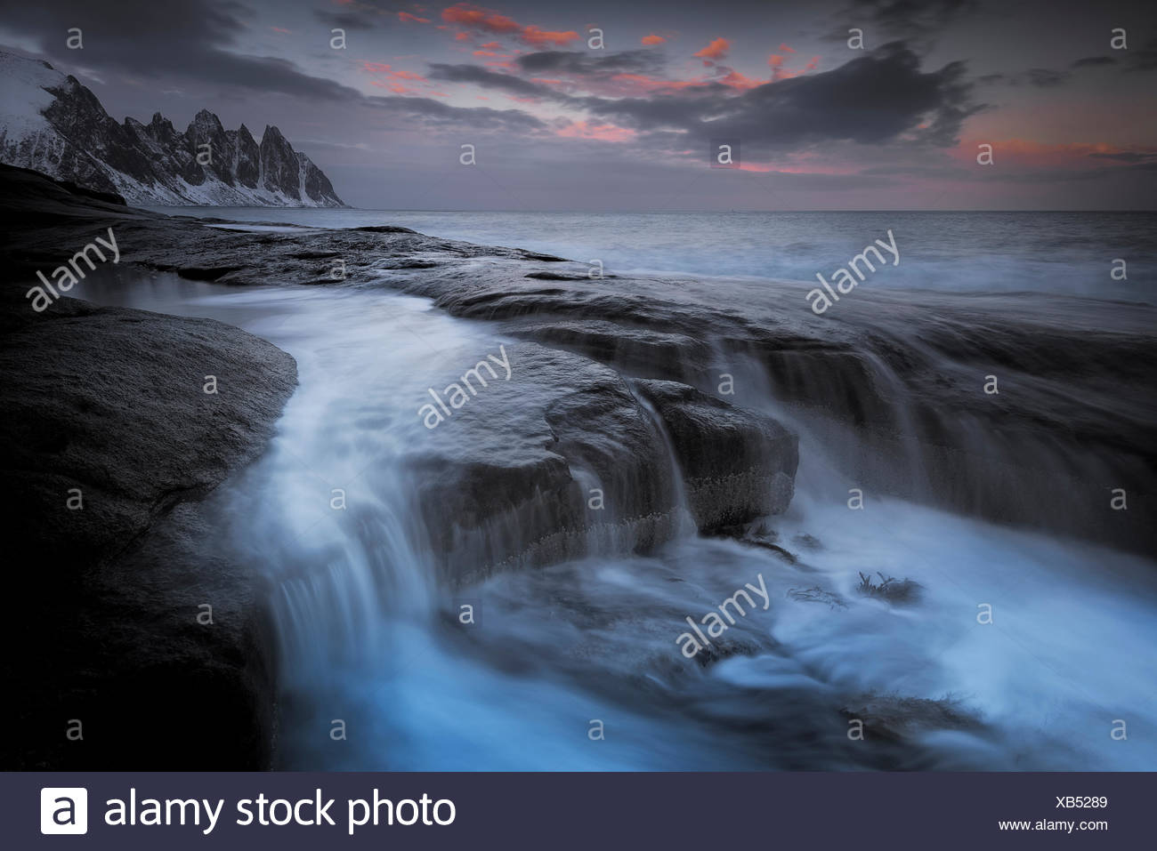 Long exposure of tidal water flowing off rocks, with the Okshornan Mountains in the background, Isle of Senja, Troms, Norway, Fe - Stock Image