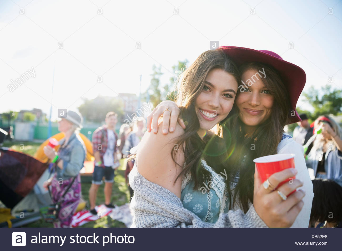 Portrait smiling young women drinking and hanging out at summer music festival campsite - Stock Image