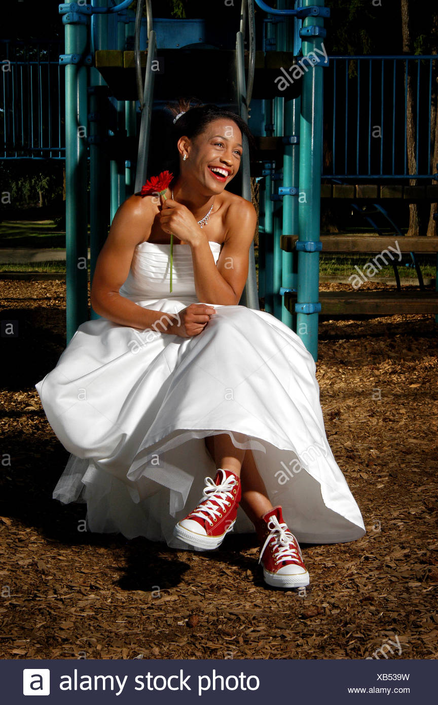 Happy, laughing bride sitting on playground equipment in wedding dress and sneakers - Stock Image