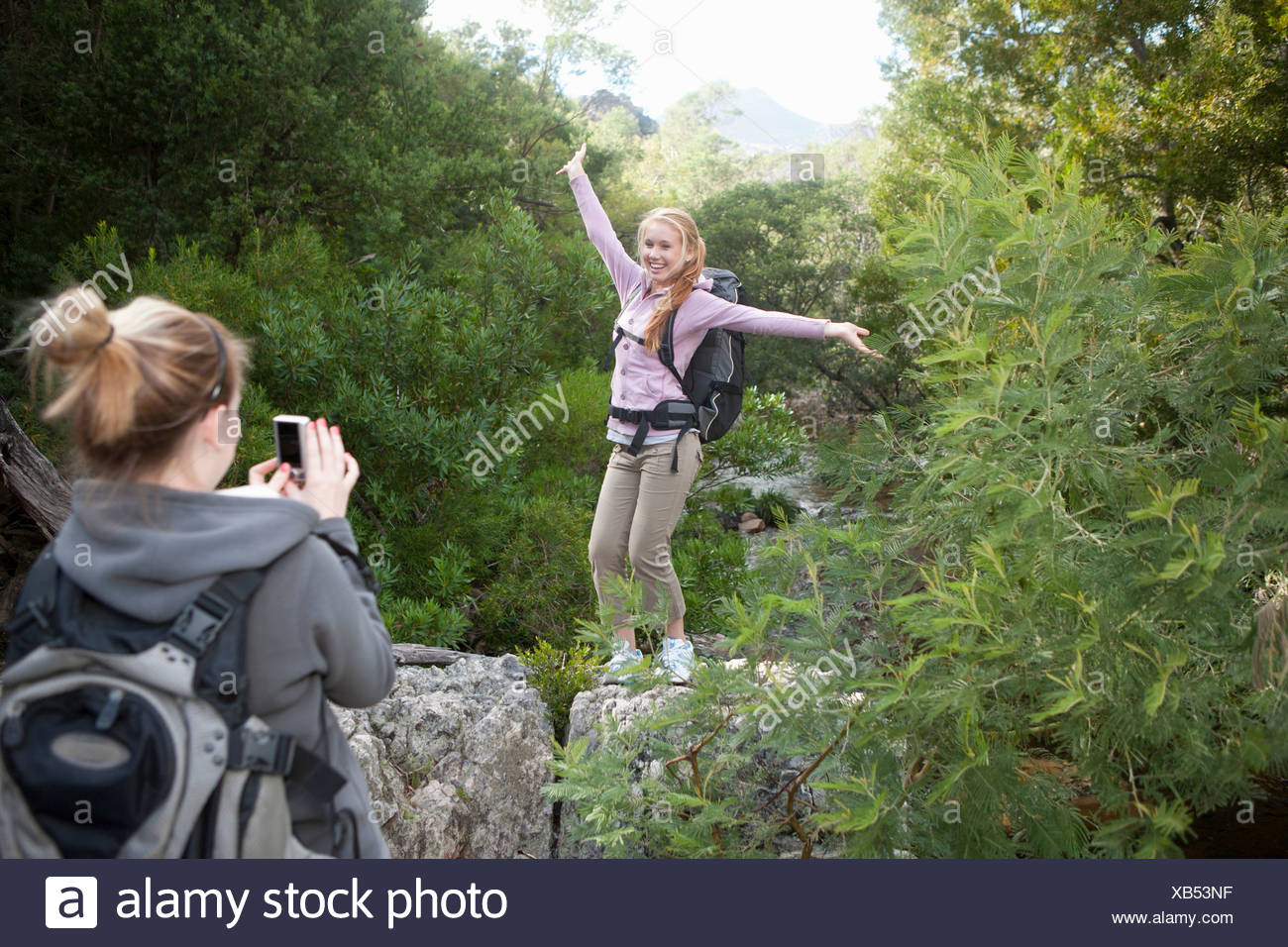 Girl hikers photographing each other on rock - Stock Image