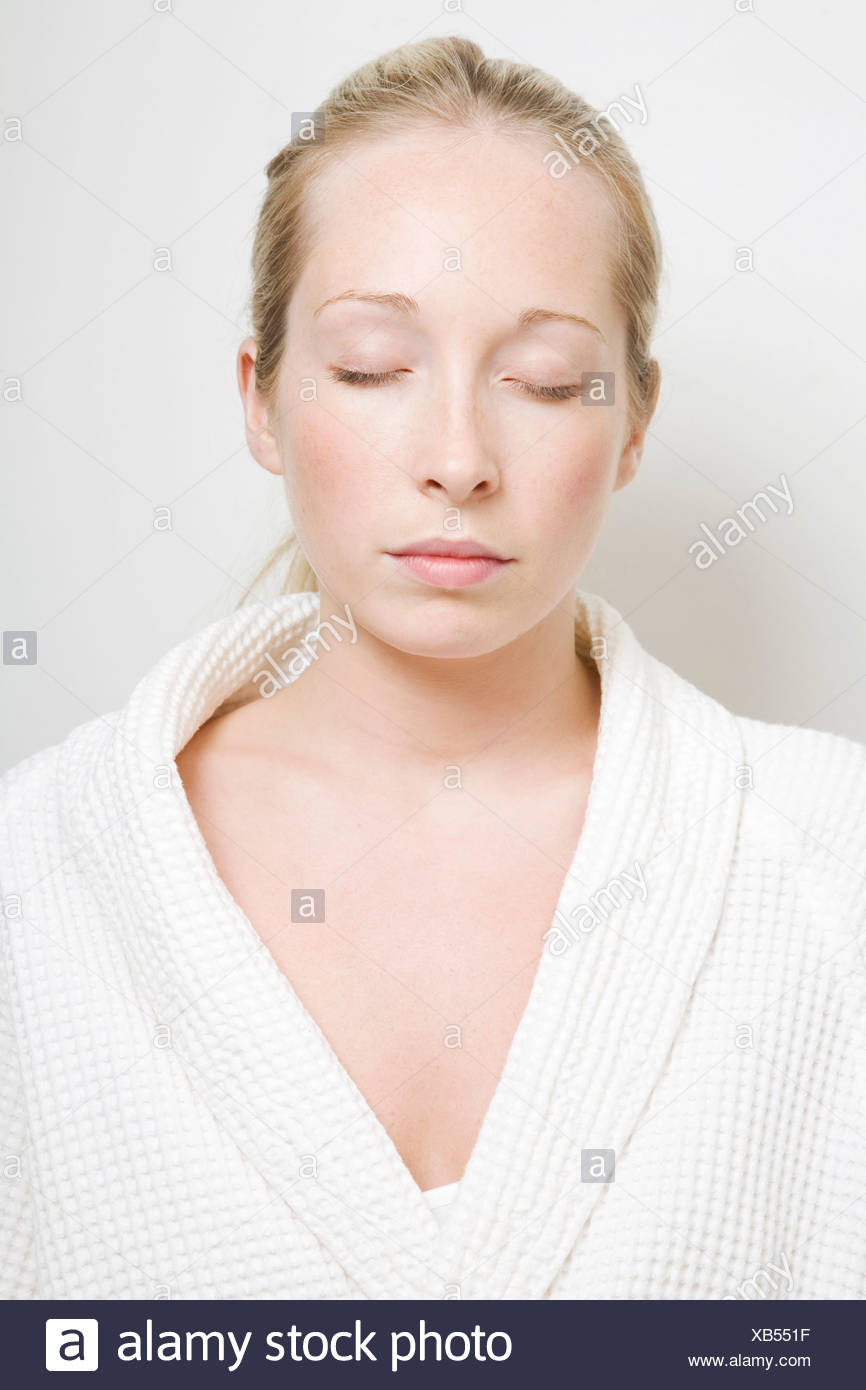 Woman wearing bathrobe with eyes closed Stock Photo