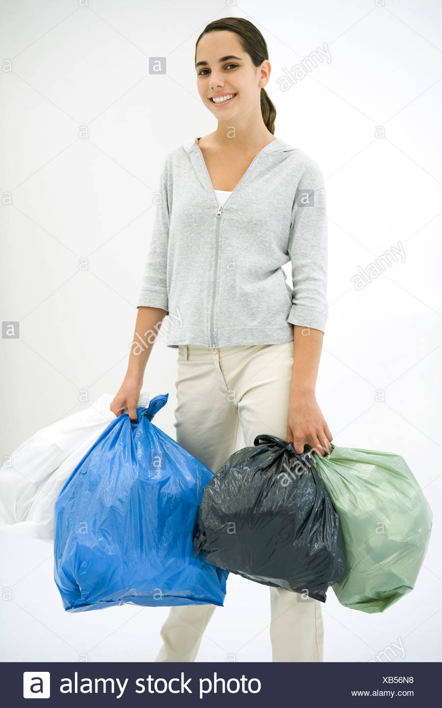 Teen girl carrying several garbage bags, smiling at camera - Stock Image