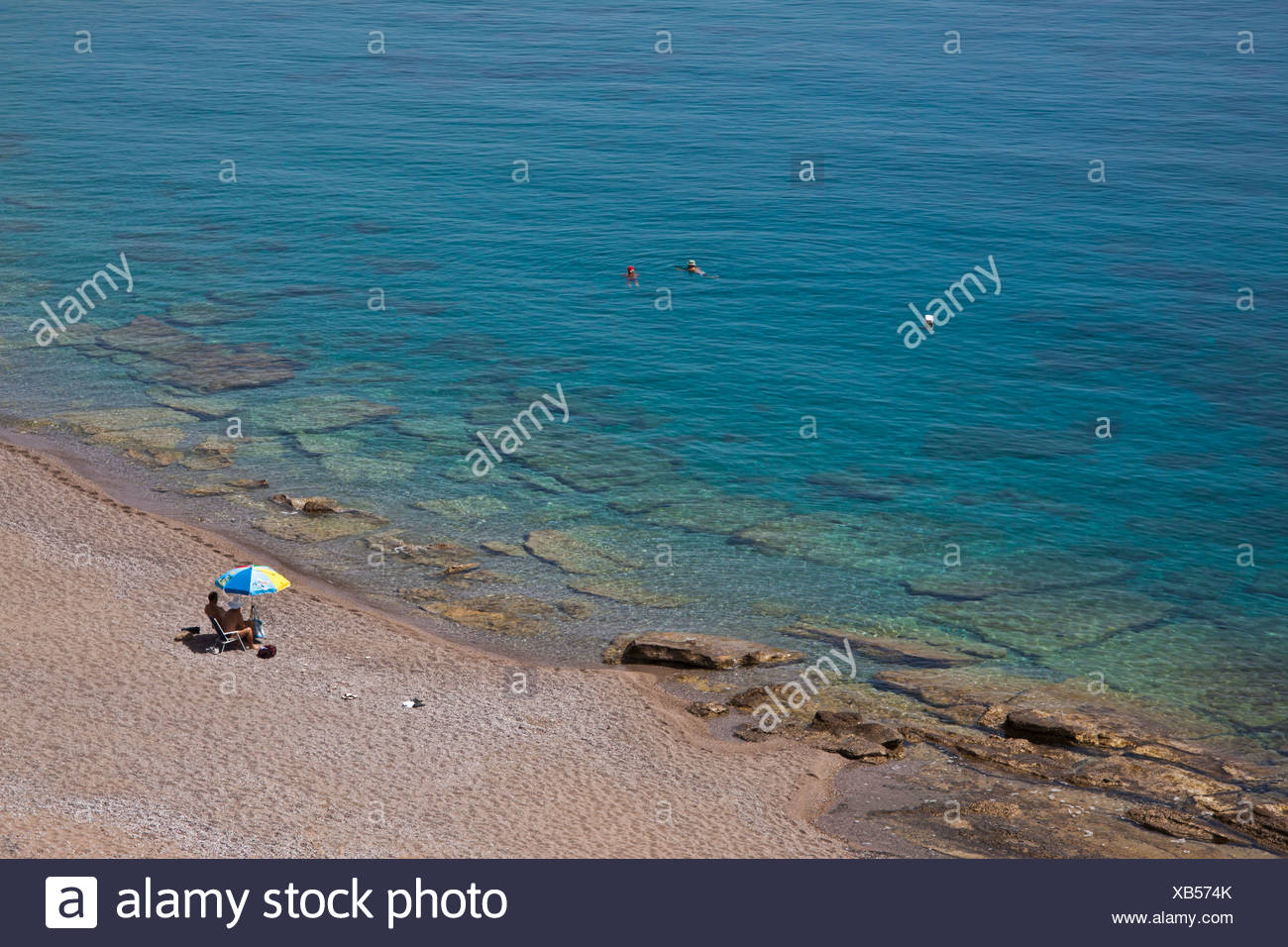 Beach, individual bather with a sunshade, Rhodes Island, Greece, Europe - Stock Image