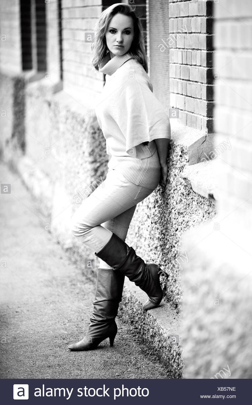 Woman leaning against a wall, wearing boots, tight trousers and a loose jumper - Stock Image