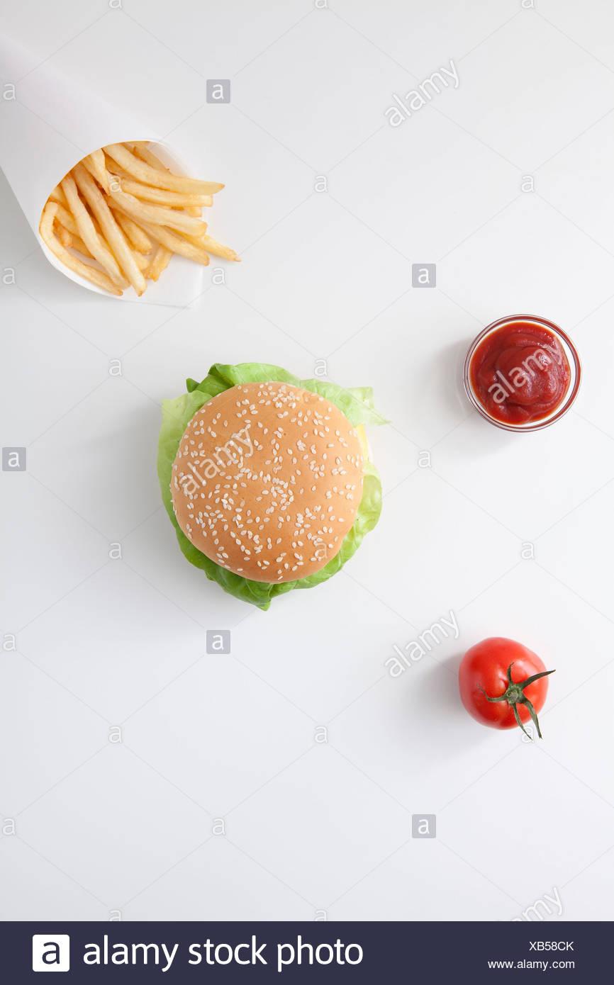 Fast food, burger, fries, ketchup, tomato - Stock Image