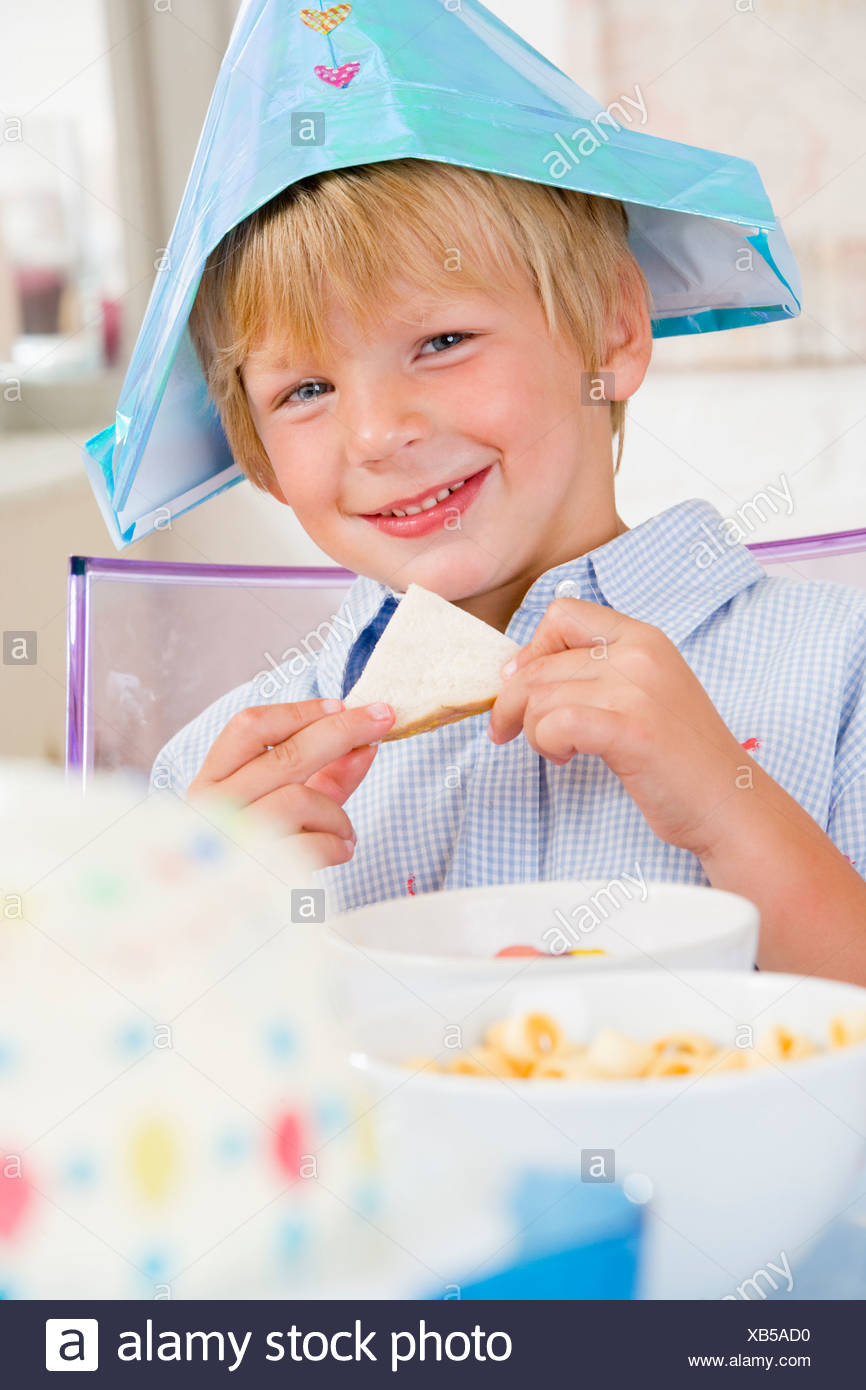 Young boy at party sitting at table with a sandwich smiling - Stock Image