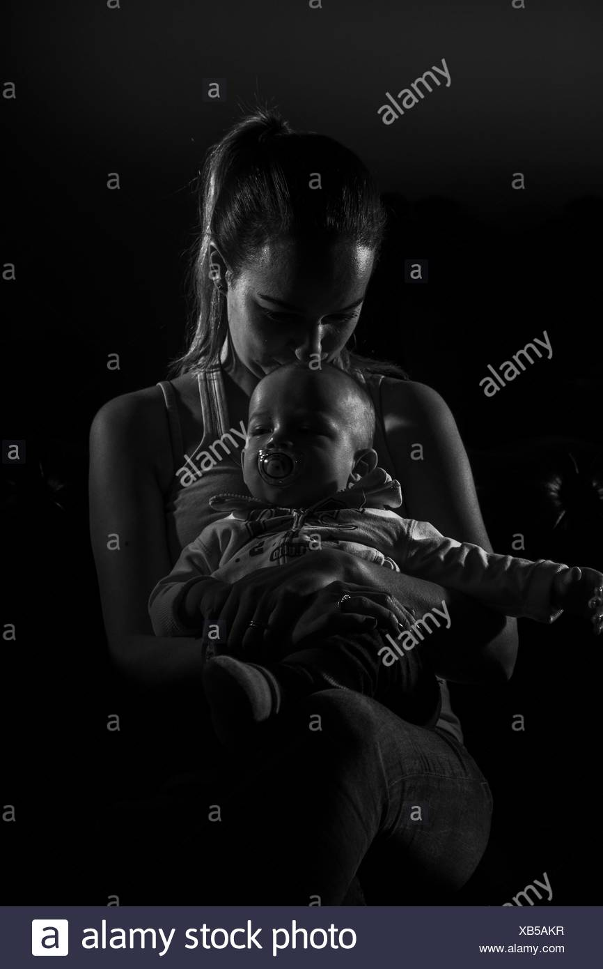 Overtired single mother with her baby - Stock Image