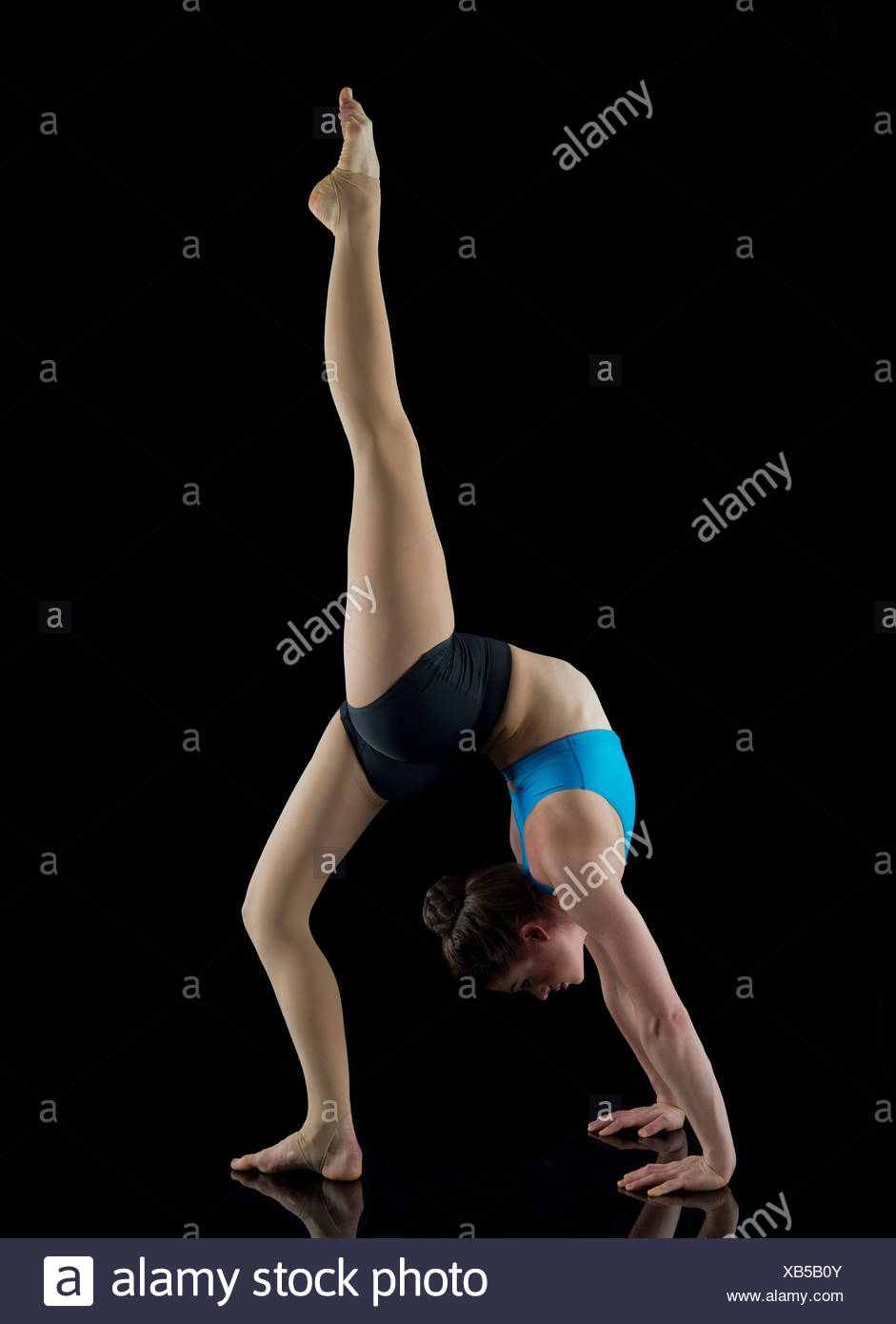 Acrobat performing in front of black background - Stock Image